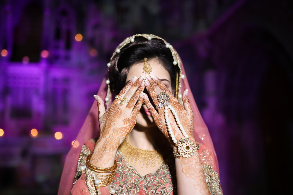 Asian bride holding her hands up so show henna. Manchester Monastery wedding photography
