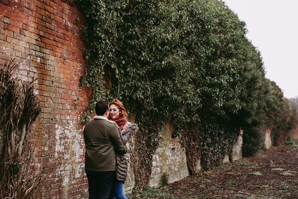 Documentary photo of couple in front of red brick wall. Haigh Hall, Lancashire