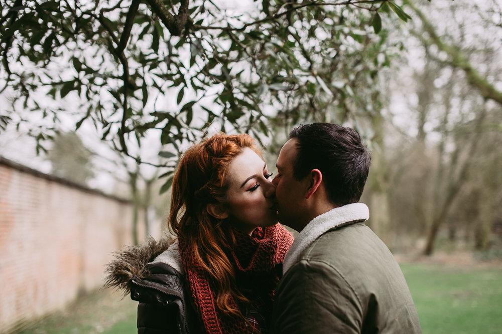 Natural photograph of couple kissing under a tree at Haigh Hall