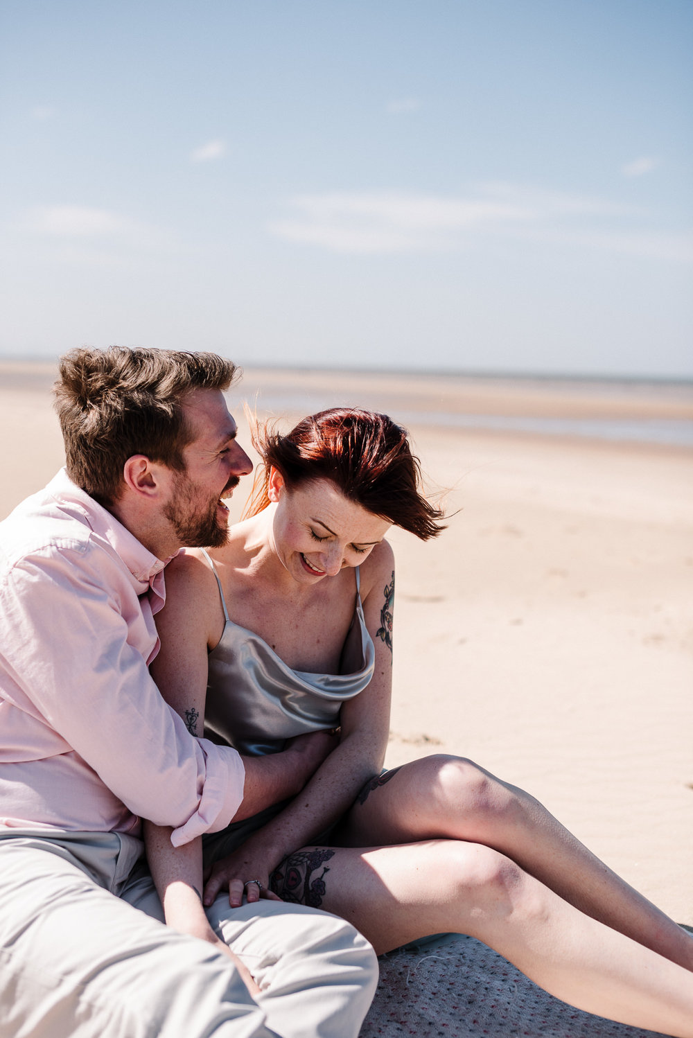 Bride and groom sat together on the sands at Formby Beach, Liverpool.