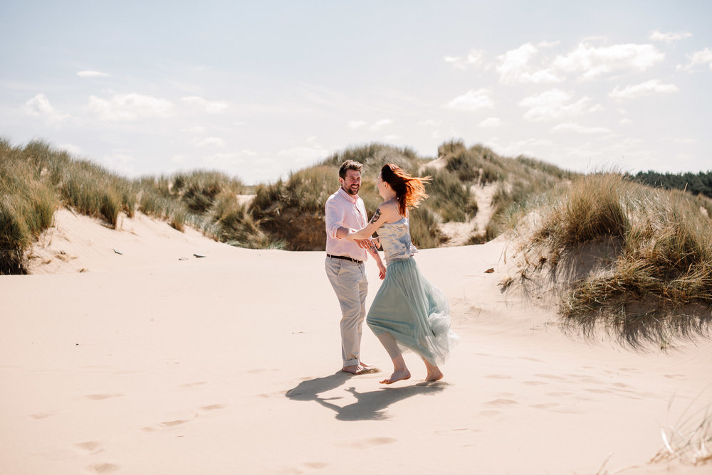 Natural shot of bride and groom dancing on the sand dunes. Beach wedding photography, Liverpool