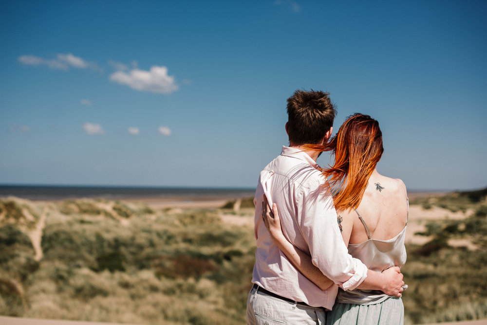 Bride and groom looking out to sea from the sand dunes on Formby beach. Liverpool wedding photography