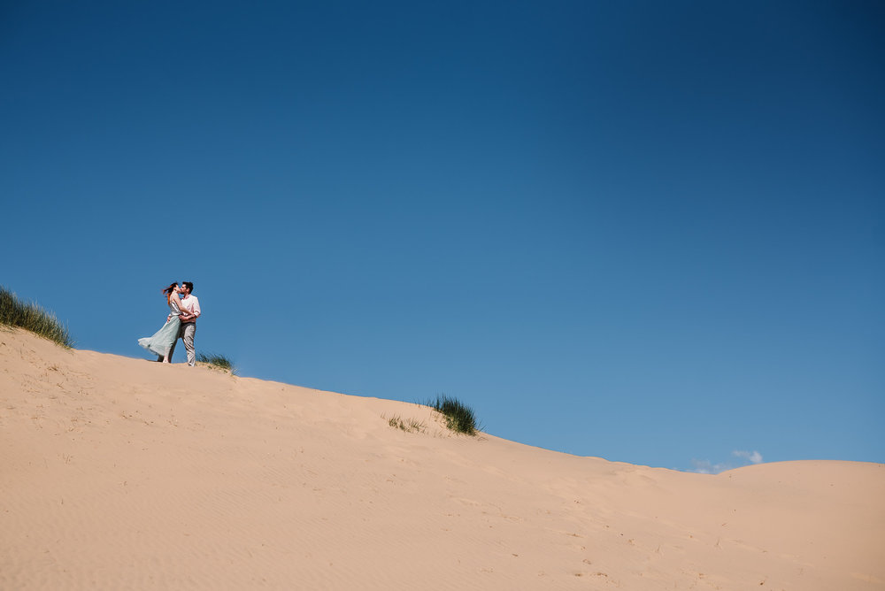 Landscape photo of bride and groom at the top of sand dune. Beach Wedding photography