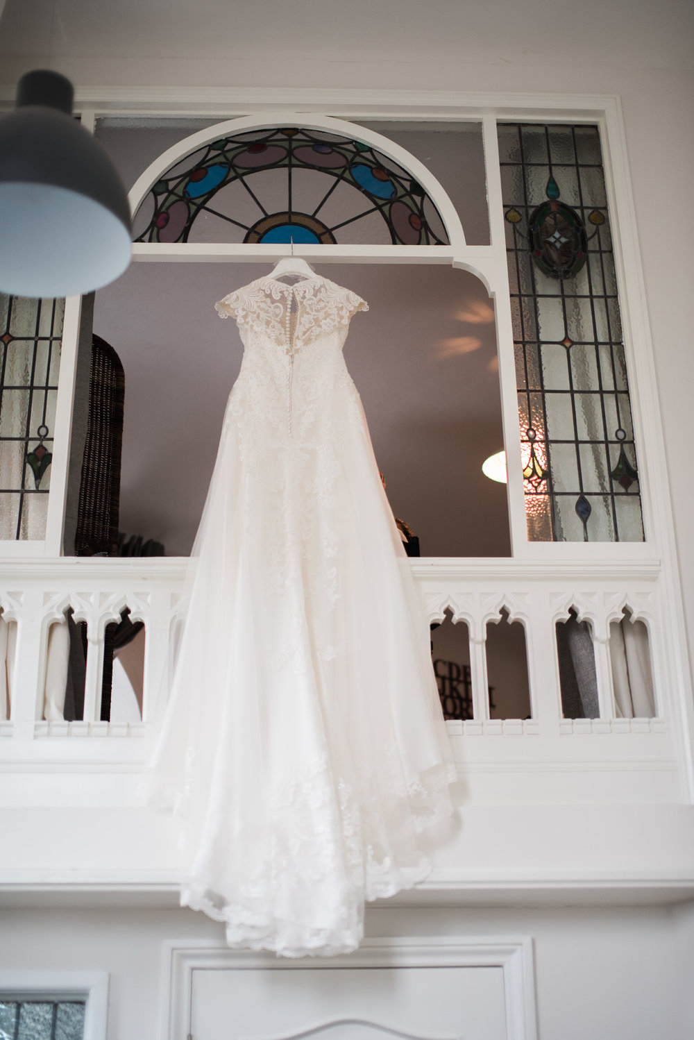 Full length shot of wedding dress hung from a window in the Dreamcatcher.