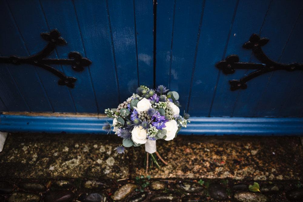 Wedding flowers up against blue door of the wedding venue