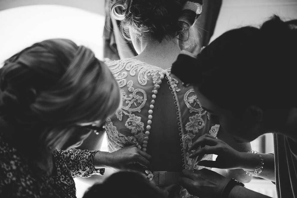 black and white photo of the brides wedding dress being buttoned up by her bridesmaids at the Dreamcatcher in Cornwall.