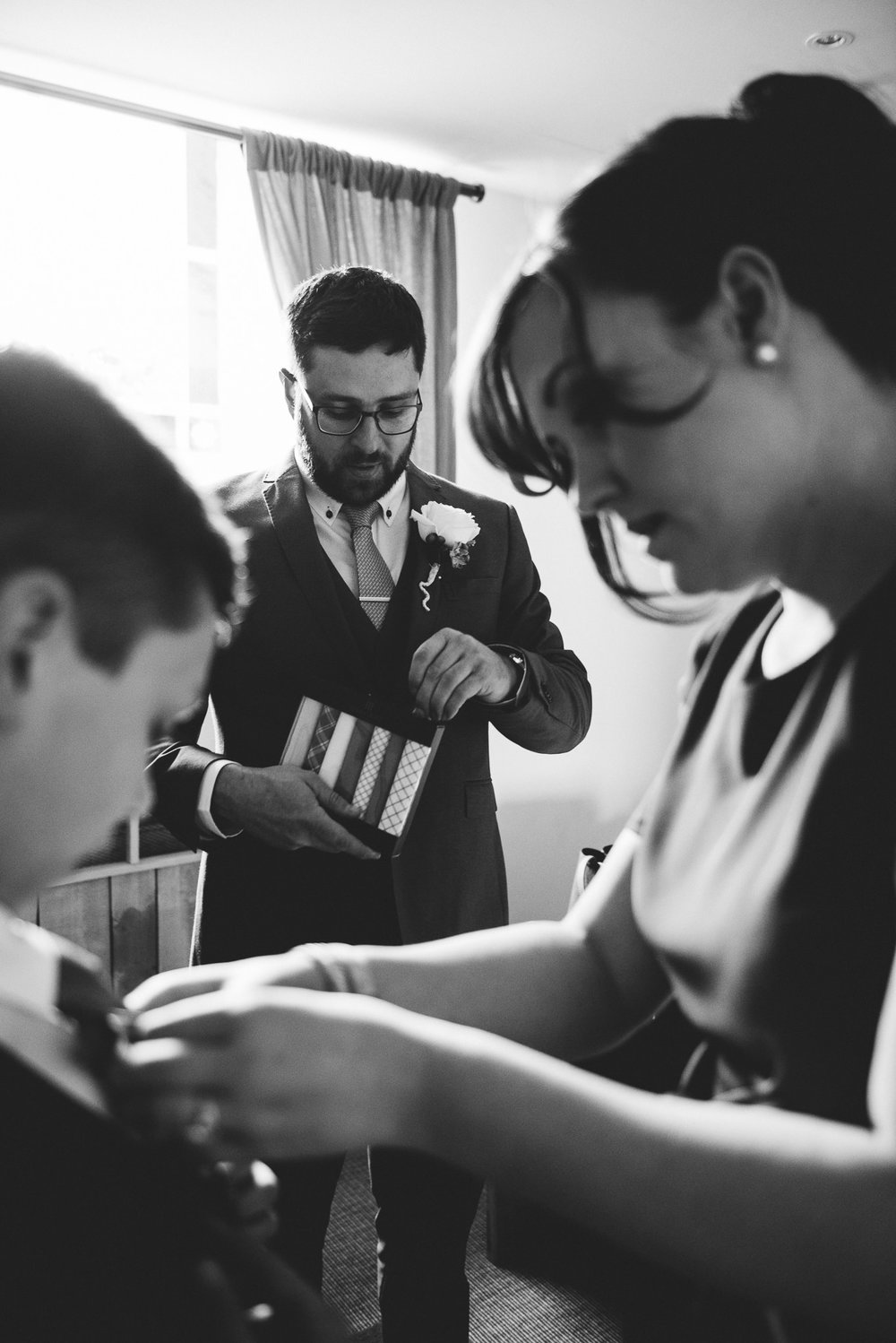 Natural shot of the Groom opening his wedding gift from bride.