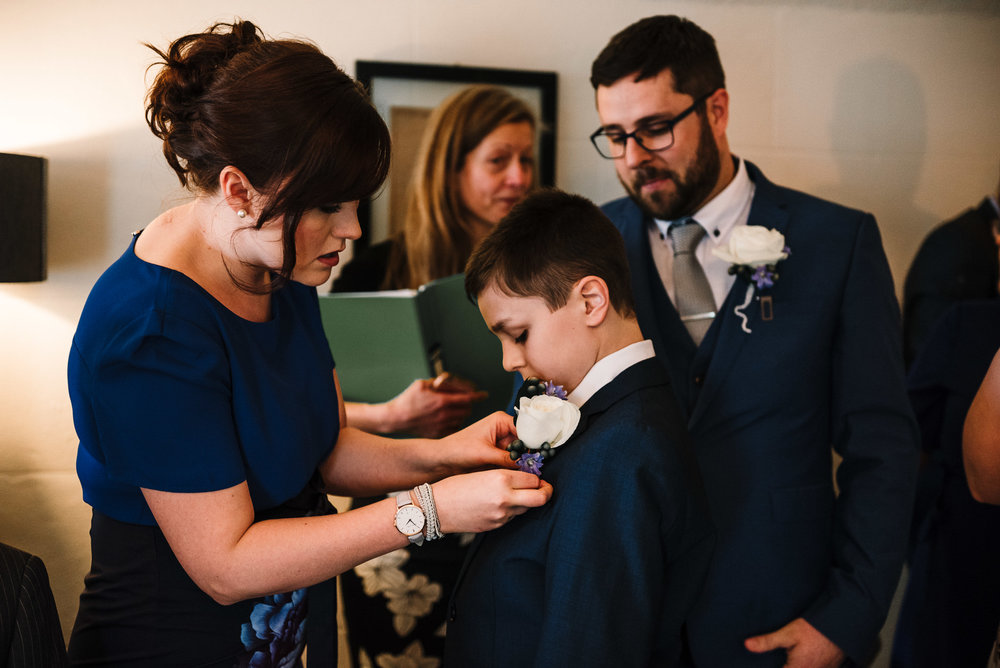 Pageboy having his button hole put on.