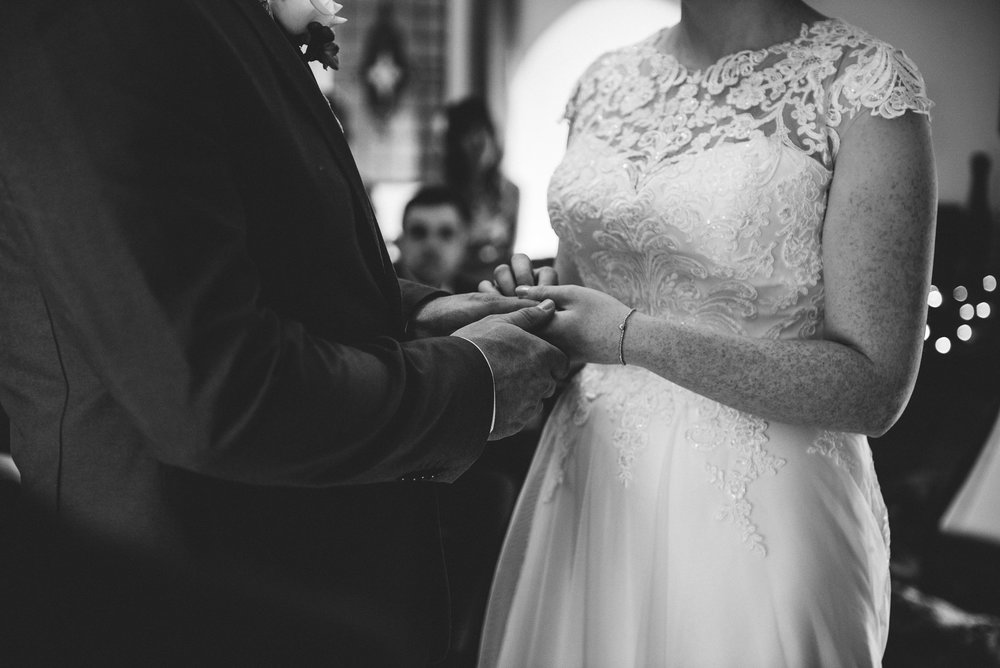 Natural shot of couple exchanging wedding rings