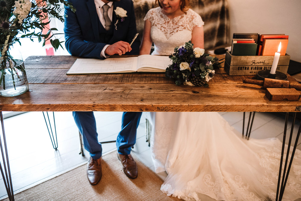 Mordern styled shot of couple signing the wedding register. Elopement wedding photography in Cornwall.