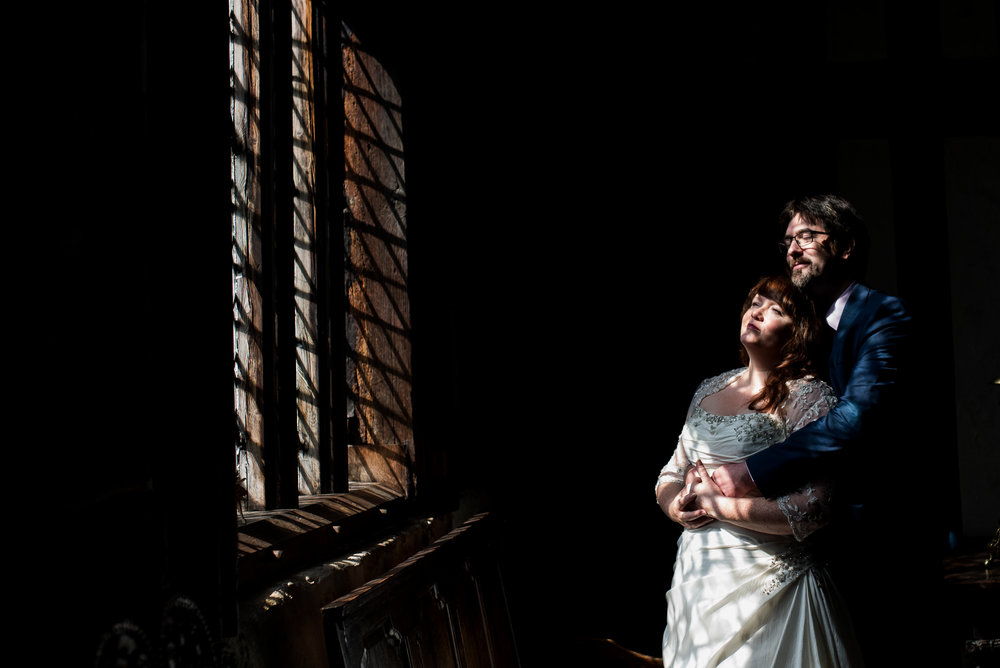 Bride and groom by the window at Rufford Old Hall in Lancashire.