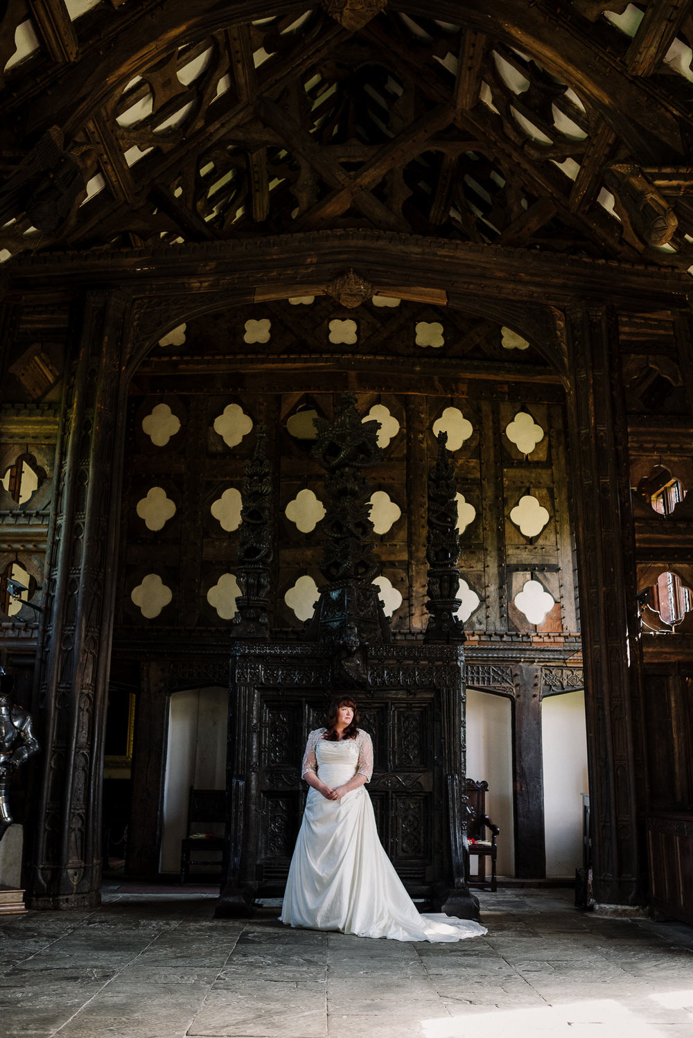 Bride in front of carved oak screen at Rufford Old Hall.
