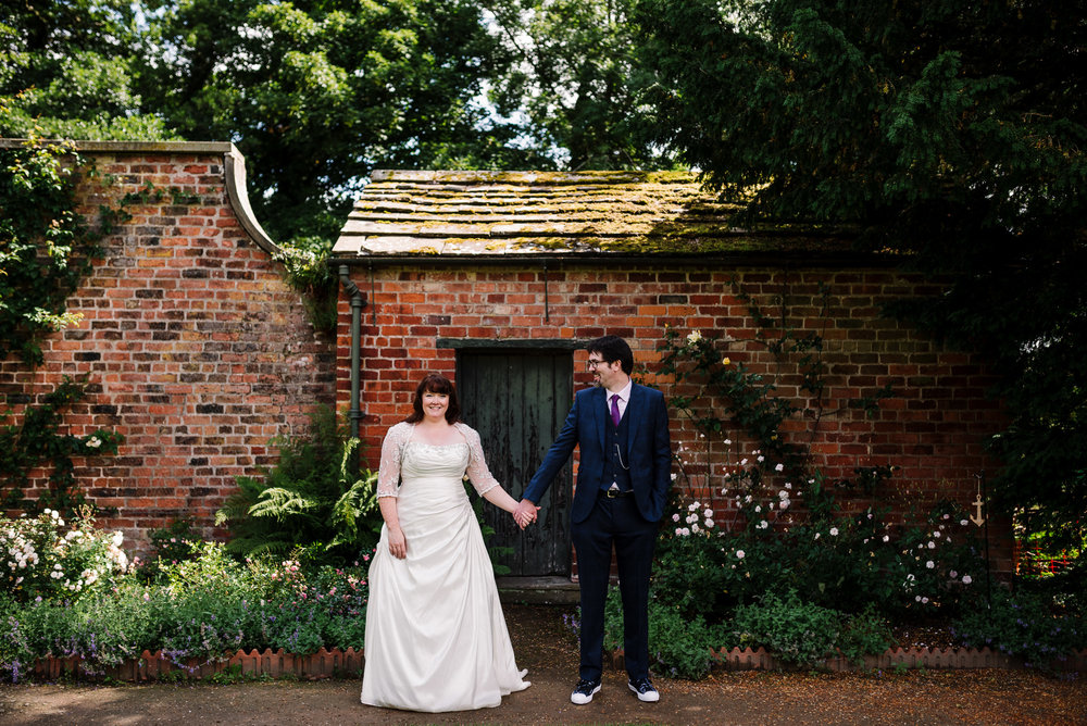 Stood holding hands in the garden. Rufford Old Hall wedding photography.