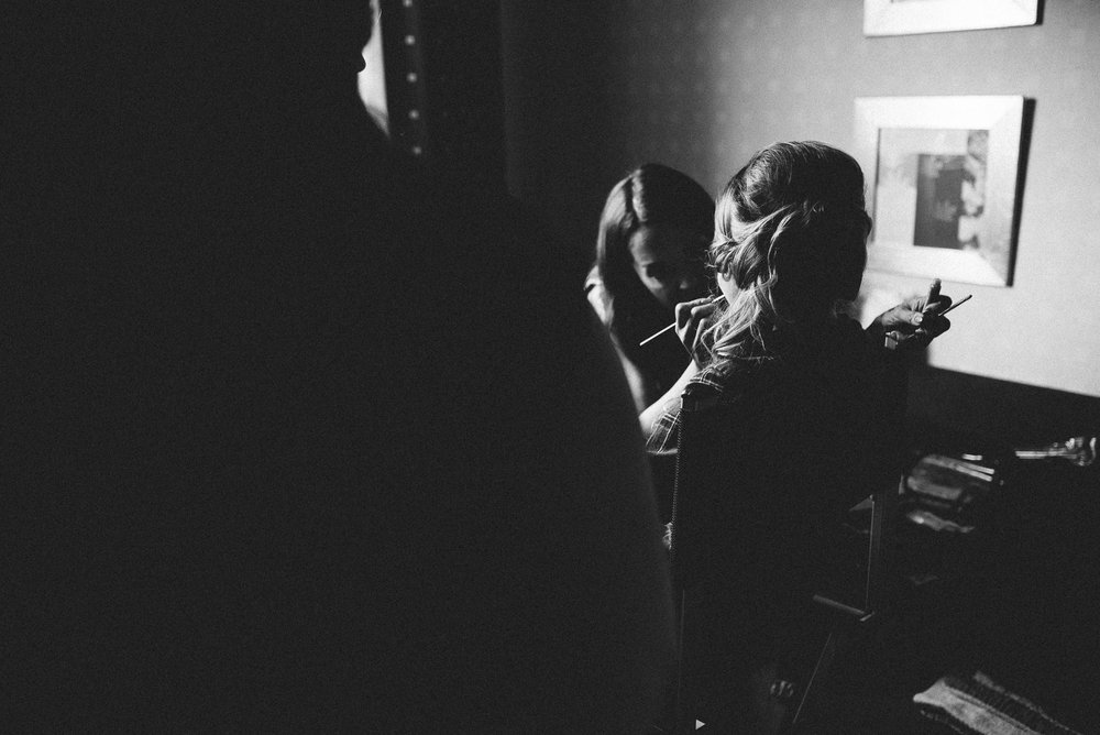 Black and white photo of bridesmaids makeup being done.
