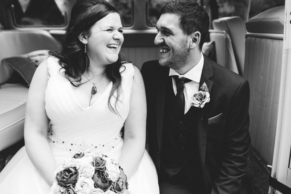 Natural shot of bride and groom laughing together.