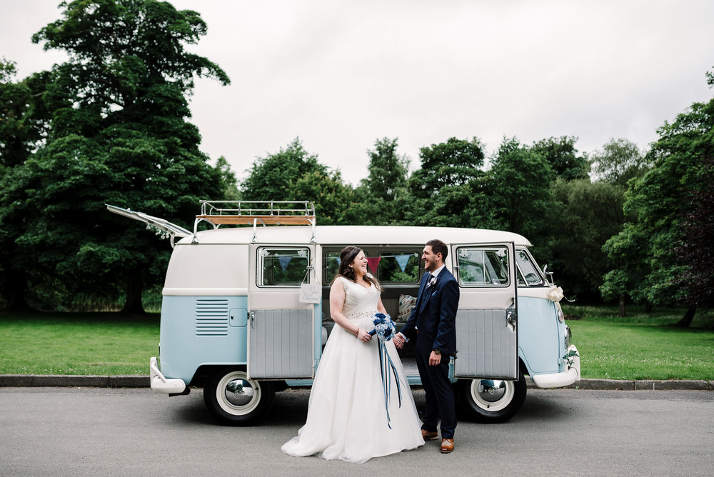 Portrait of bride and groom stood together outside of the VW camper van.