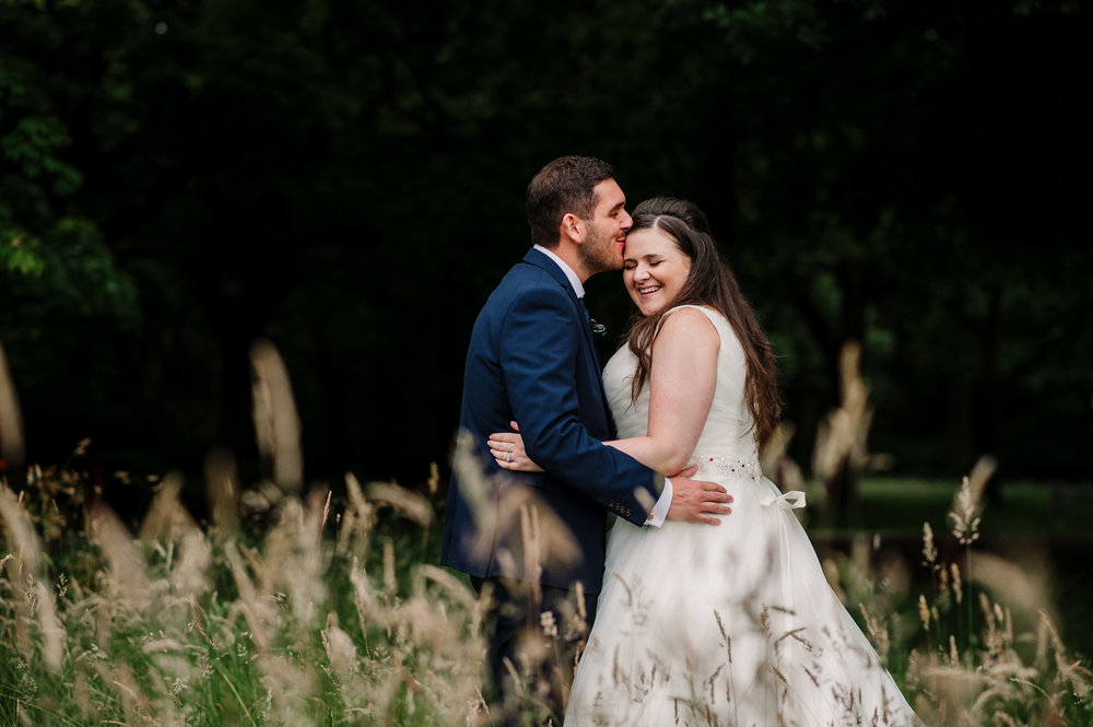 Natural photo of the bride and groom in long grass. Rivington Hall Barn wedding photography.