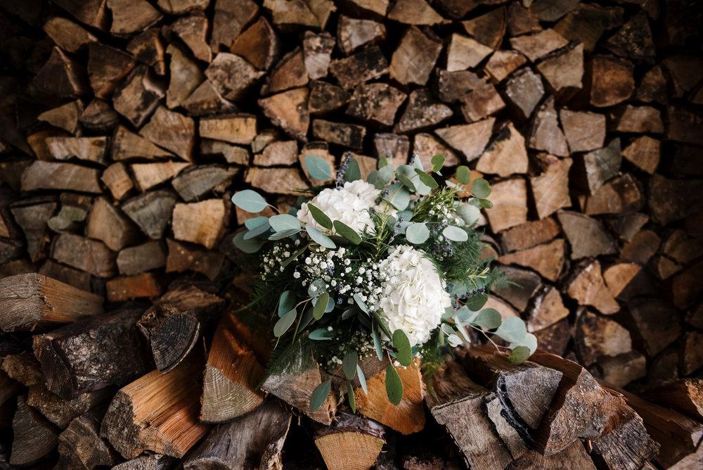 Brides bouquet on log pile. Farm wedding photography
