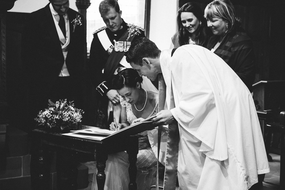 black and white documentary shot of the bride signing the register