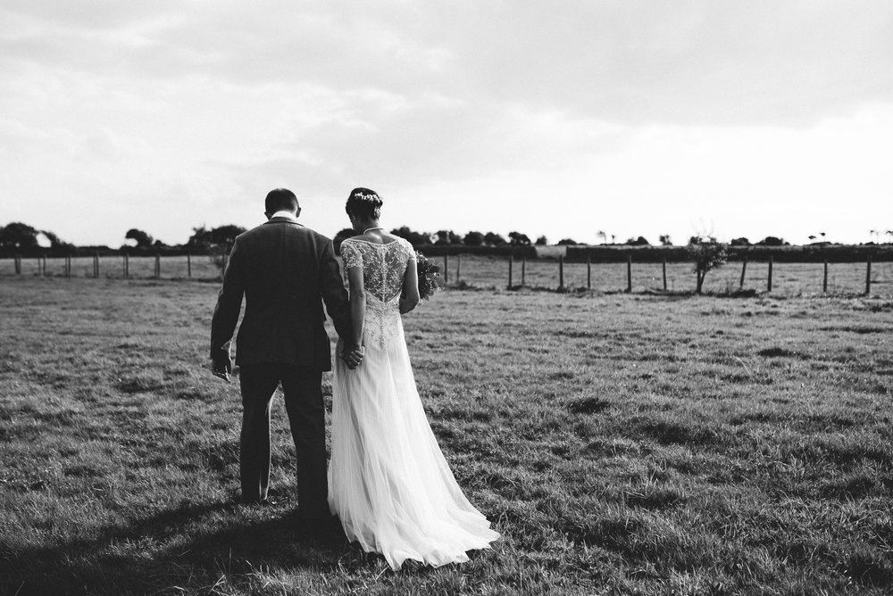 Natural black and white photo of bride and groom walking on the farm.