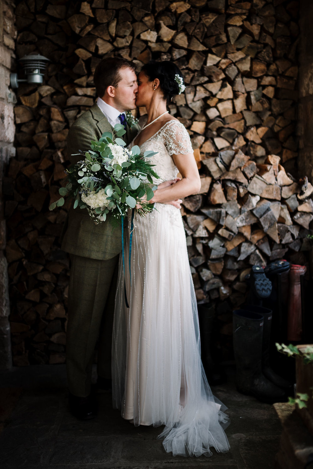 Bride and groom kissing outside the farm house.