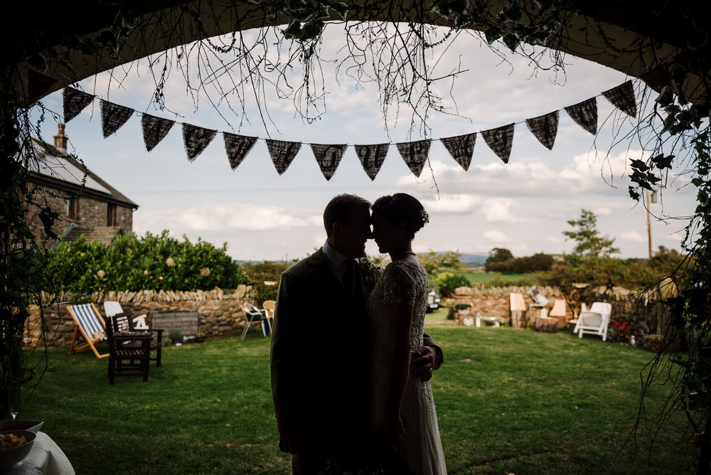 Creative wedding photography. Bride and groom silhouetted with view from the farm in background