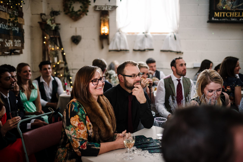 Guests laughing during speeches. Natural wedding photography in the Lake District.