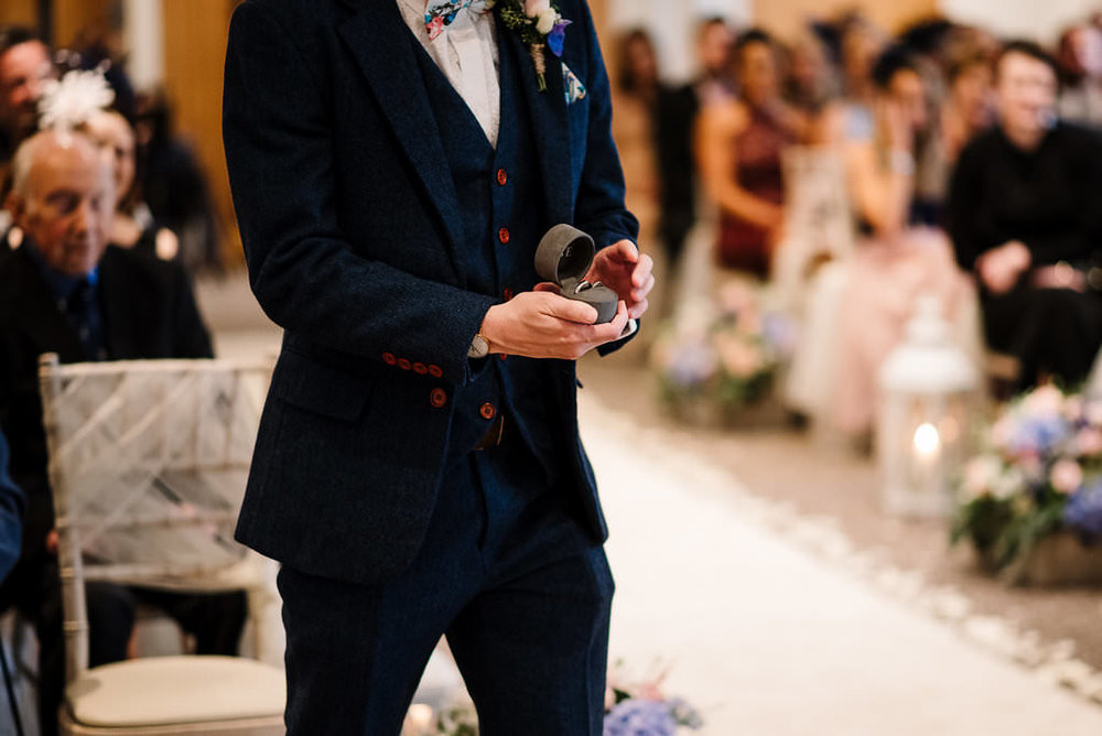 closeup shot of best man with the wedding rings. natural wedding photography
