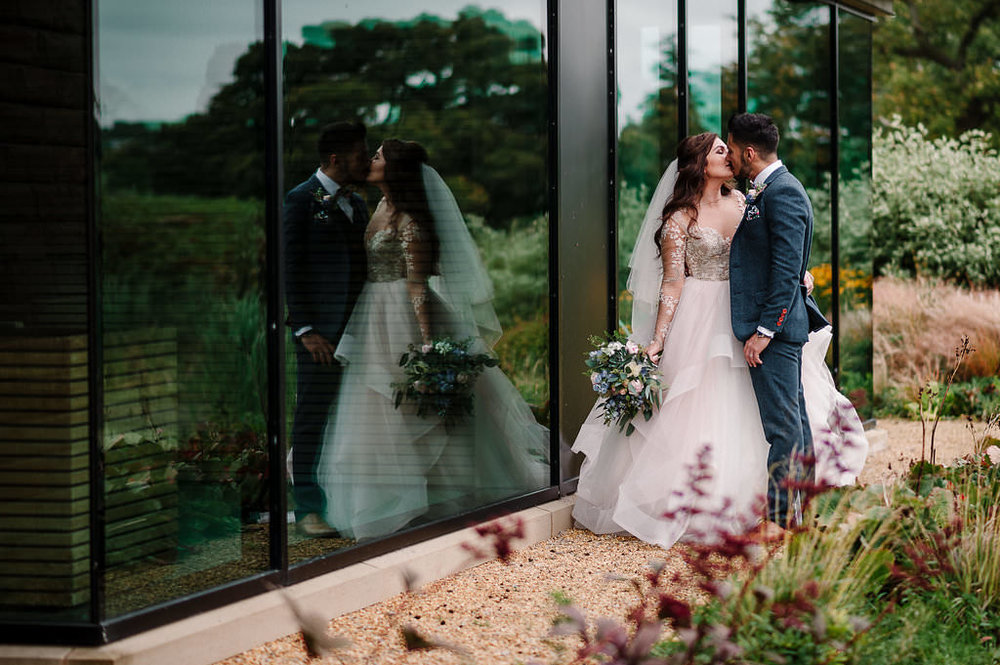 Creative portrait of bride and groom with reflection in a window. Lancashire wedding photography at Stanley House Hotel