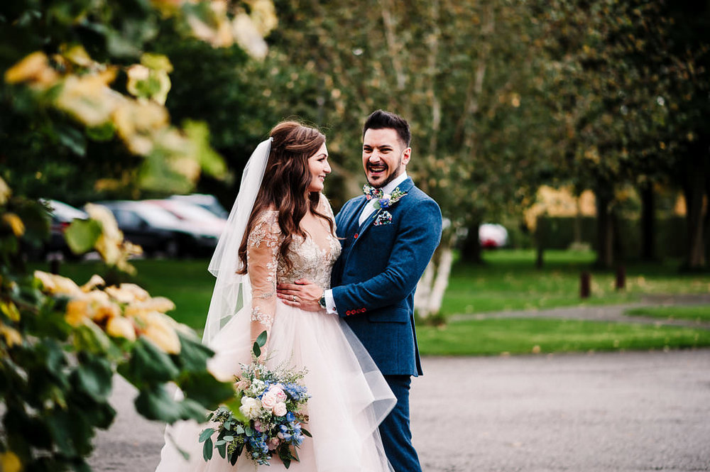 Natural shot of bride and groom laughing together
