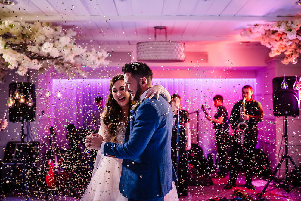 Relaxed shot of bride and groom dancing with confetti in the air. Lancashire wedding photography