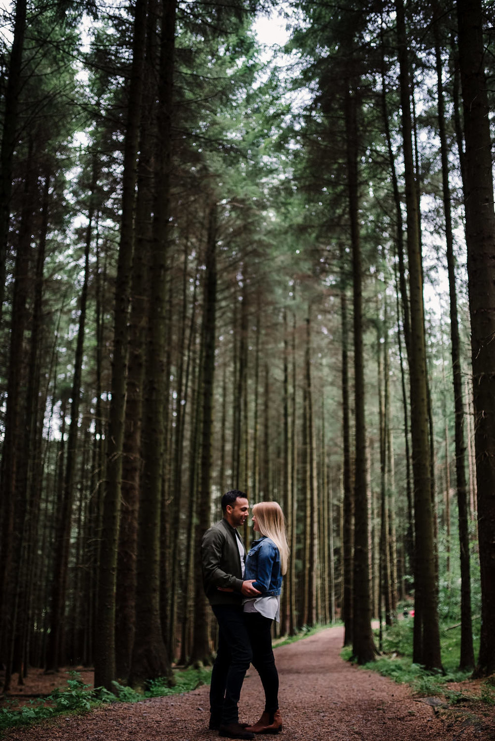 Natural photograph of couple kissing in the woods. Lancashire lifestyle photography.