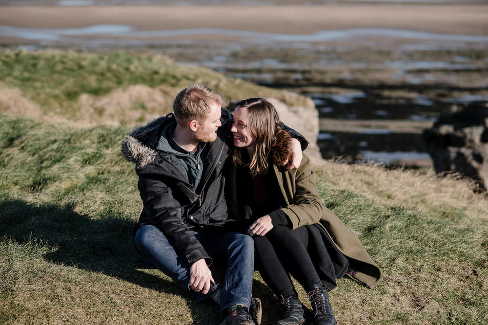 Natural photo of couple sat on the hillside at Hilbre Island.