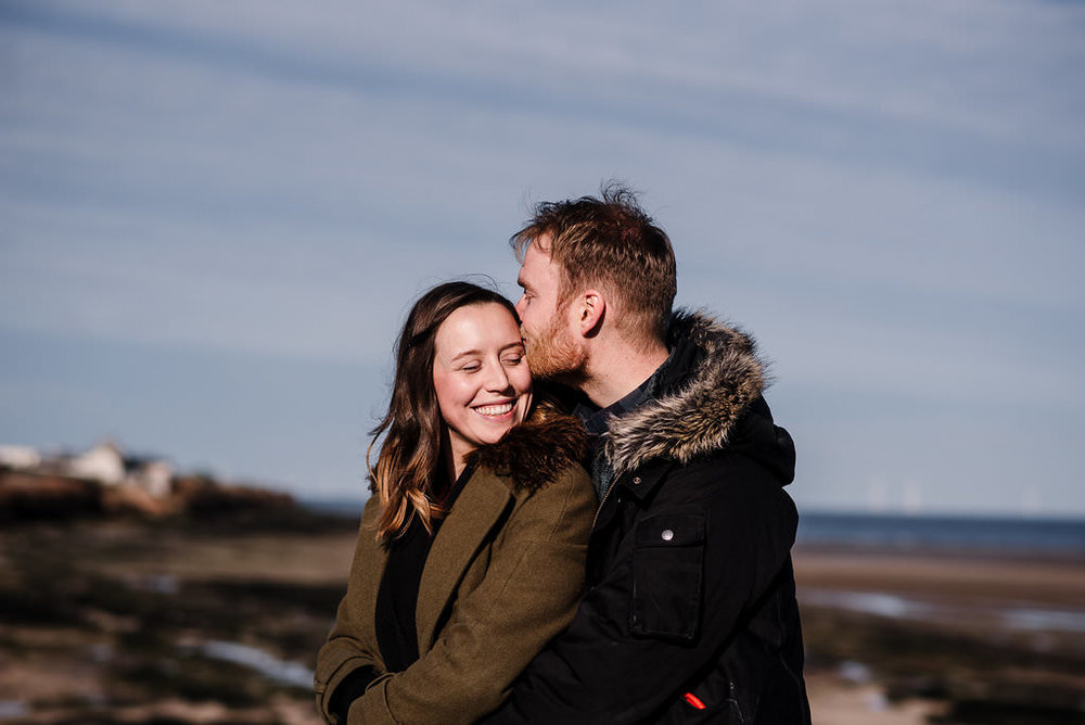 Couple hugging with landscape in the background. West Kirby engagement photography