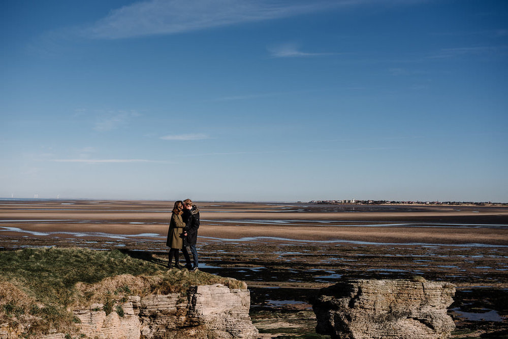 Landscape photo of inland views from Hilbre Island with couple kissing
