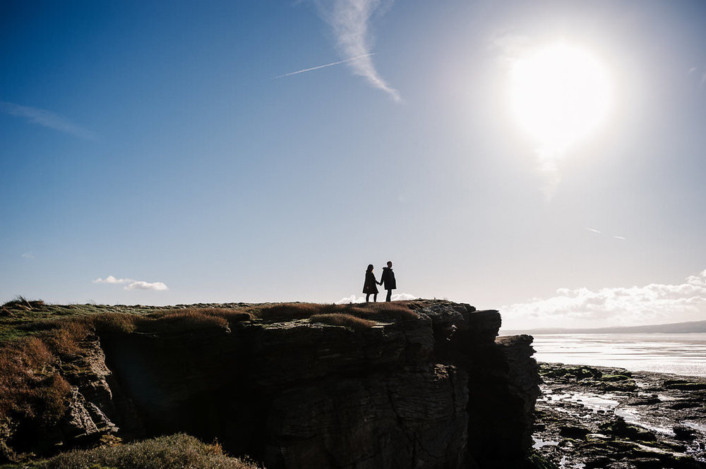 Silhouette of couple stood on cliff top. West Kirby Engagement photography