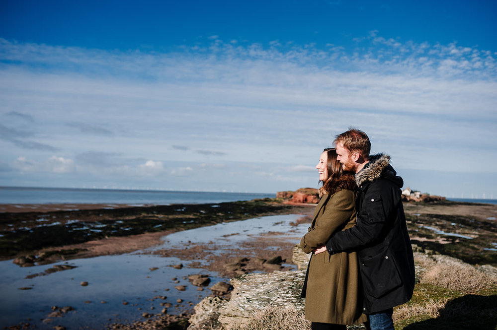 Relaxed photo of couple looking out to sea with Hilbre Island in the distance.