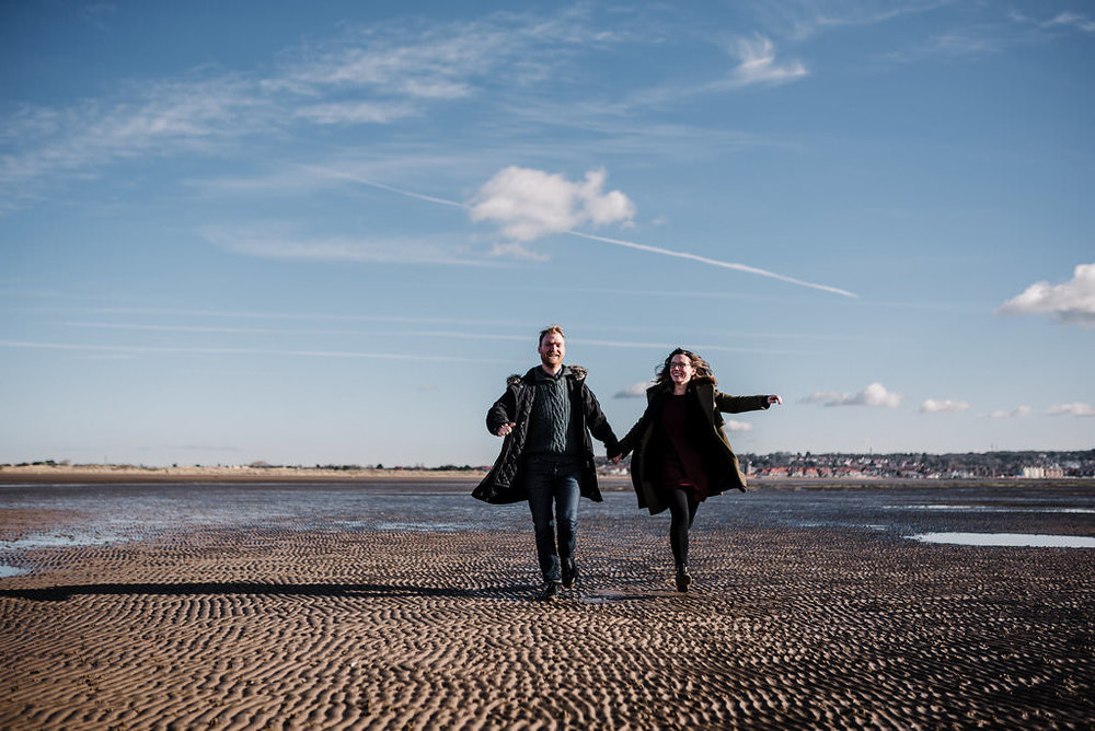 Fun shot of couple running on the beach together. West Kirby engagement photography