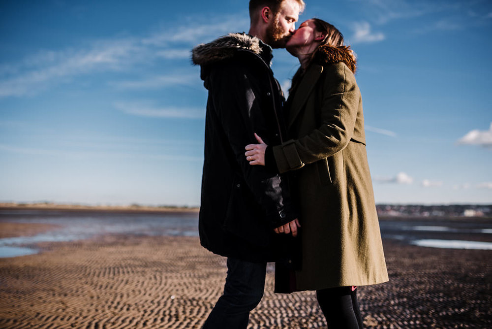Bright and colourful portrait of couple kissing on the beach in West Kirby. Engagement Photography Merseyside.