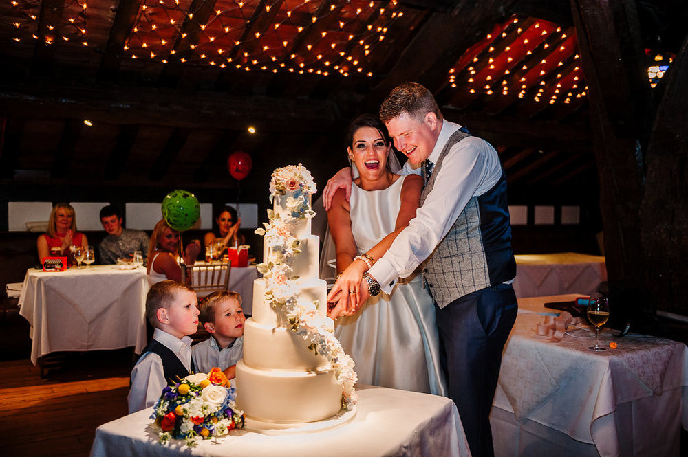 Natural photo of bride and groom cutting their cake.