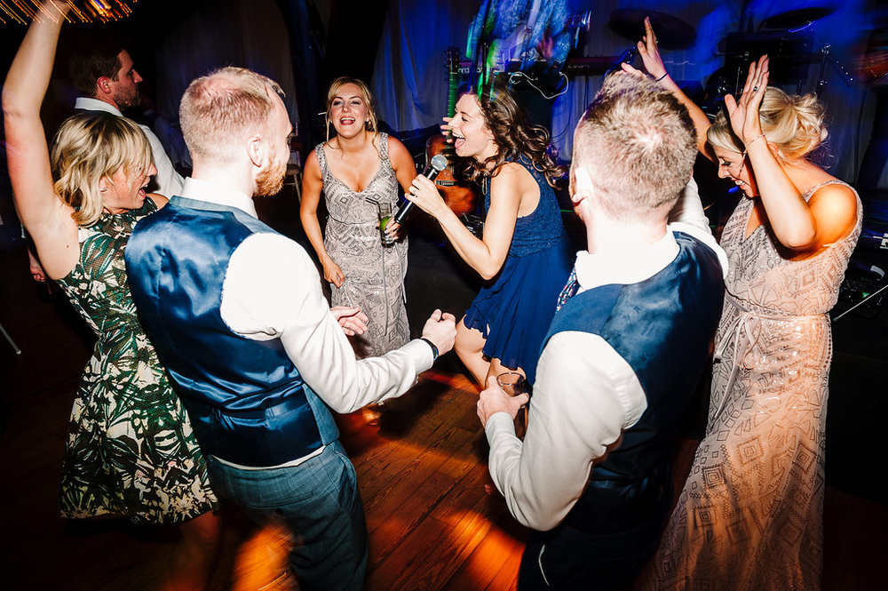 Colourful dance floor shot of guest dancing at Rivington Hall Barn wedding.