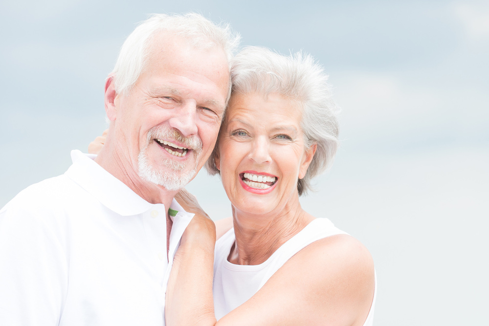 A smiling couple with hearing loss.