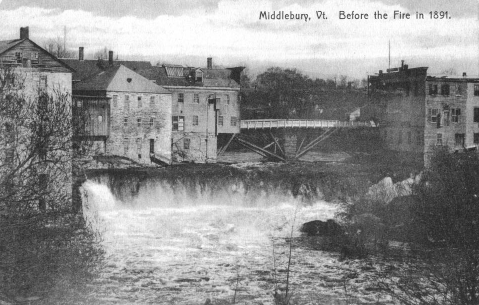 This old wooden bridge spanning Otter Creek at the falls in Middlebury, burned during the fire of 1891 and was replaced with a sturdier stone one built by Joseph Battell.