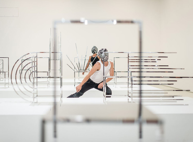 Masked dancers, James Batchelor, Melanie Lane, and Jessie Oshodi, perform work by Antony Hamilton within Oki Sato's fifty  Manga chairs , as part of Chunky Move's  Accumulation  at NGV Triennial, photographed by Eugene Hyland