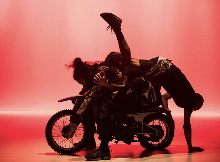 Jahra Rager, Sarah Vai, and Tyrone Robinson, balanced atop of and becoming a part of a Yamaha PeeWee50, in Amrita Hepi's  A Caltex Spectrum , KCA, Dancehouse, by Gregory Lorenzutti