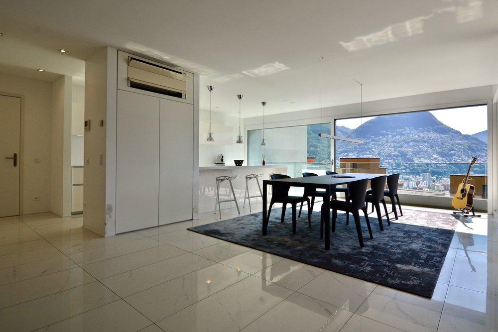 Cucina e sala pranzo con vista sul lago. Appartamento moderno a Lugano in vendita in posizione strategica con stupenda vista sul Lago di Lugano.