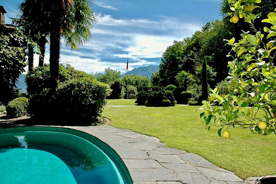 Swimming Pool with view to the large garden and lake. Villa at Lake Maggiore, Switzerland for sale.