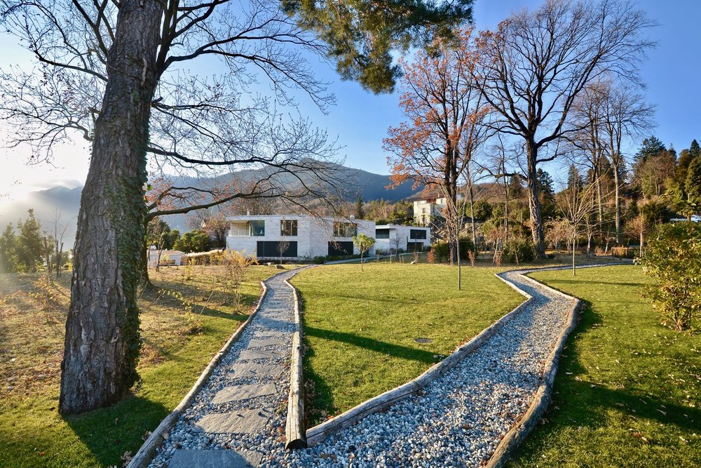 Parco privato con imponenti alberi secolari. Appartamento attico in zona dominante ad Ascona, Svizzera, in vendita con vista sul Lago Maggiore.