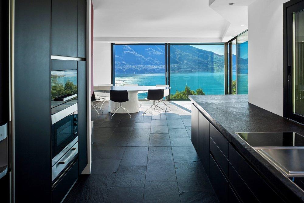 Blick von der Küche ins Wohnzimmer mit Seeblick. Modernes Designer-Haus in Minusio mit Blick auf den Lago Maggiore zu verkaufen