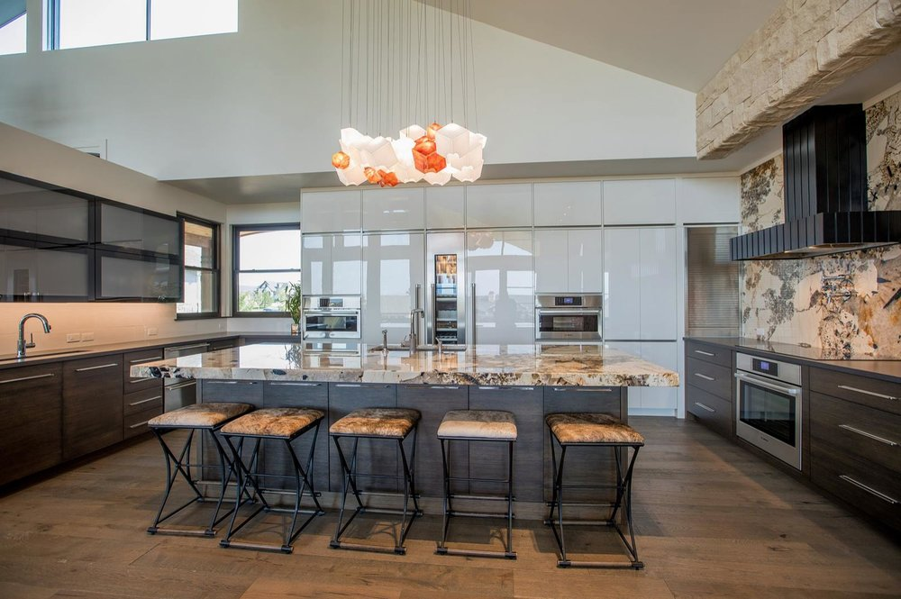 This kitchen features; Lift up doors, white high gloss acrylic, and a mix of wood species.  Truly a transitional style througout.
